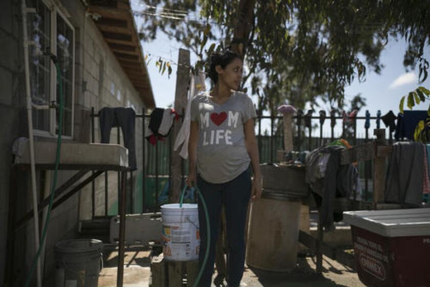 En esta imagen del 23 de mayo de 2019, la adolescente migrante embarazada Milagro de Jesús Henríquez Ayala llena un cubo con agua en el refugio de la iglesia Ágape Misión Mundial en Tijuana, México.