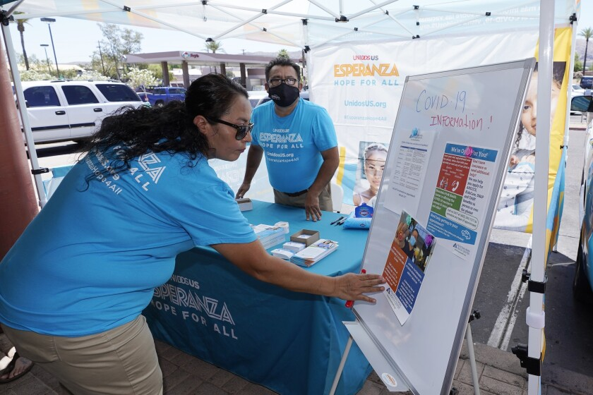 FILE - In this May 7, 2021, file photo, Sonia Lorenzana, left, and Jose Marquez, right, of UnidosUS, set up an informational tent display, increasing efforts to bring more vaccine doses into Latino neighborhoods, at a local shopping plaza in Phoenix. Latinos in the U.S. were hard hit by the pandemic both financially and personally, but many feel generally optimistic that the worst is behind them, according to a new study by the Pew Research Center. (AP Photo/Ross D. Franklin, File)