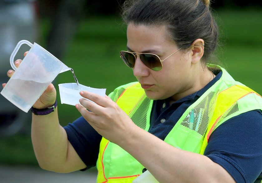 FILE - In a May 14, 2016 file photo, Mouttet from the Corpus Christi Utilities Department collects a sample of water to test on the corner of Claremore St. and Kentner St. in Corpus Christi, Texas. The Texas Gulf Coast city has issued three orders in less than a year telling residents to boil their