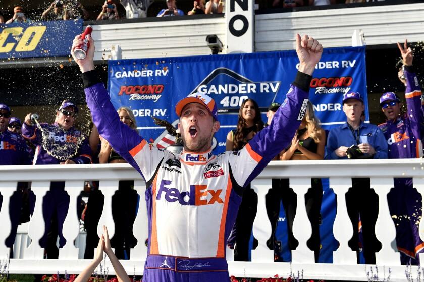 Denny Hamlin celebrates after winning Sunday's NASCAR Cup race at Pocono Raceway.