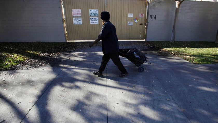 A person walks past the gate of a South L.A. facility operated by AllenCo Energy Co. in this 2013 file photo. AllenCo has suspended operations at the site for the past five years.