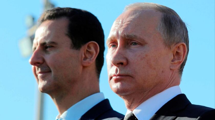 Russian President Vladimir Putin, right, and Syrian President Bashar Assad in December watch the troops marching at the Hemeimeem air base in Syria. Putin's government denies Russian mercenaries killed in Syria worked on behalf of Russia.