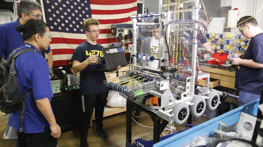 Avery Levin from Marina High, makes final adjustments on his mechanical robot for team Surf City Vik