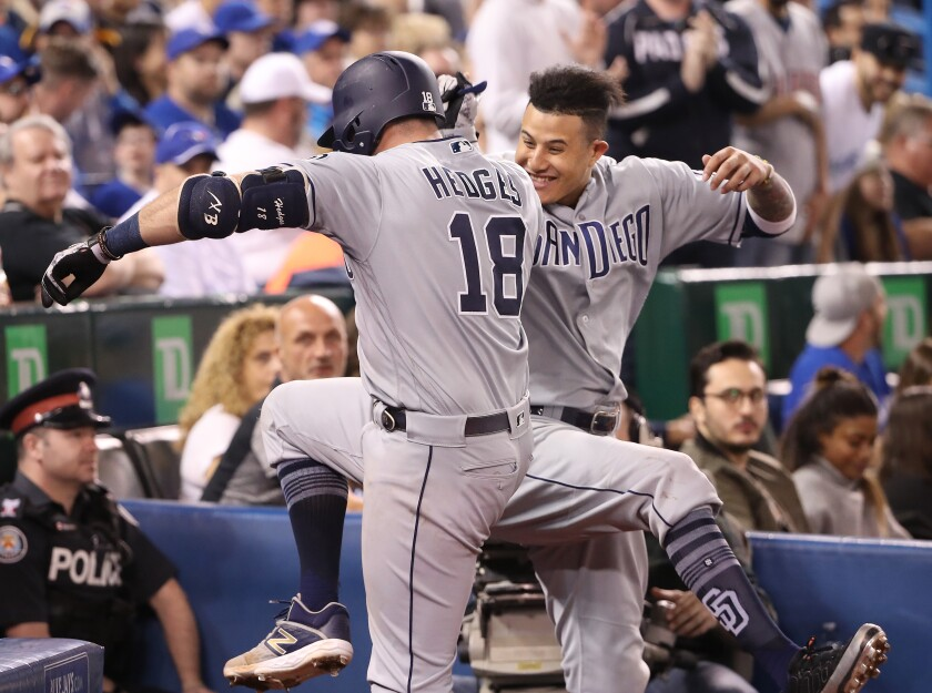 Austin Hedges and Manny Machado celebrate after Hedges' grand slam in the fourth inning of the Padres' 19-4 victory over the Blue Jays on Saturday.