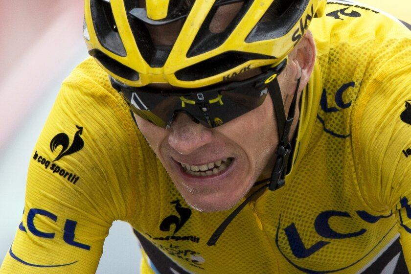 FILE - In this July 24, 2015, file photo, Britain's Chris Froome, wearing the overall leader's yellow jersey, grimaces as he crosses the finish line of the 19th stage of the Tour de France cycling race over 138 kilometers (85.7 miles) with start in Saint-Jean-de-Maurienne and finish in La Toussuire, France. Froome will be racing both for and against history when the Spanish Vuelta starts Saturday, Aug. 22, 2015. The Tour de France champion will be aiming to become the third cyclist to win both the Tour and the Vuelta in the same season. But to join Jacques Anquetil (1963) and Bernard Hinault (1978) as the only riders to complete the rare double, Froome will have to finally win the Grand Tour that has left him with runner-up finishes on two occasions. (AP Photo/Peter Dejong, File)