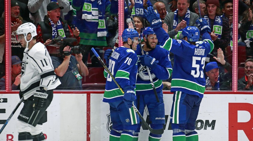 The Vancouver Canucks celebrate a goal as Kings captain Anze Kopitar skates past during the Kings' 8-2 loss Wednesday.