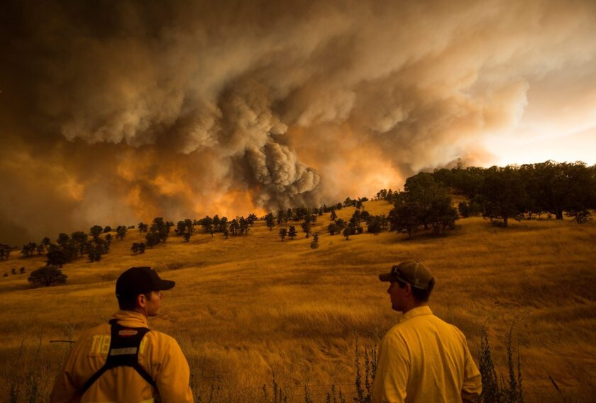 Firefighters watch as the Rocky fire burns near Clearlake, Calif., on Aug. 1.