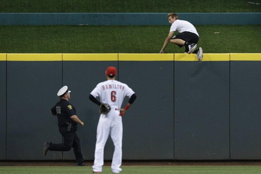 FILE - In this Wednesday, July 22, 2015, file photo, a fan climbs over the center field wall as he evades police while Cincinnati Reds center fielder Billy Hamilton (6) looks on in the eighth inning in the second game of a baseball doubleheader against the Chicago Cubs in Cincinnati. Justin Buchanan of Noblesville, Indiana, was arrested Thursday night at the Cincinnati police headquarters and is charged with criminal trespassing on a place of public amusement, a first degree misdemeanor. (AP Photo/John Minchillo)