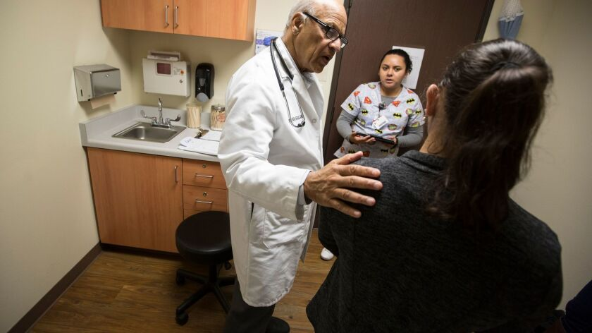 Dr. Karunyan Arulanantham, left, talks with a patient as medical assistant Marinela Castillo, center, is on hand to translate at the Antelope Valley Community Clinic in Lancaster.
