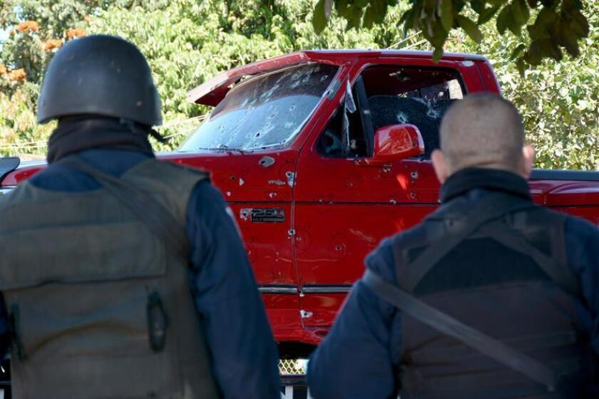 Residentes observan el vehículo que conducía un comandante de la policía estatal cuando fue acribillado la mañana de hoy, domingo 19 de febrero de 2017, en el municipio de Culiacancito, estado de Sinaloa (México). El vehículo que conducía la víctima, identificada con el nombre de Jesús Ríos, asignado al cuerpo Elite de la policía, fue impactado con por lo menos 200 tiros de fusil AK-47, informó la Procuraduría General del Justicia. Horas despues de este suceso, la policía fue alertada nuevamente luego de que en un paraje del municipio de Novolato habían hallado el cuerpo del que fuera comandante de la policía municipal de la población de Las Bebelamas, Eusebio N, que se encontraba desaparecido desde las ocho de la mañana de hoy, cuando había finalizado su turno.EFE