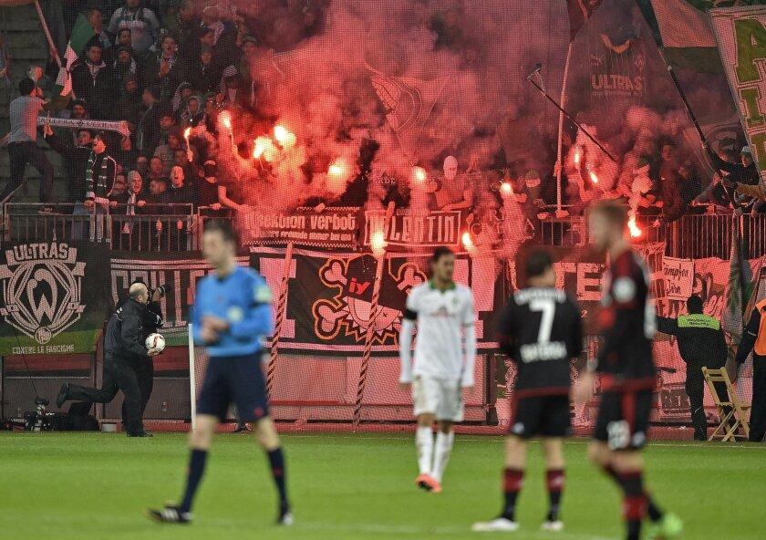 Bremen supporters burn fireworks during the  German Soccer Cup quarterfinal match between Bayer Leverkusen and Werder Bremen in Leverkusen, Germany, Tuesday, Feb. 9, 2016. (AP Photo/Martin Meissner)