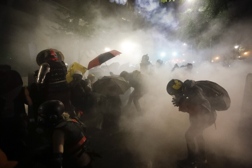 Federal officers launch tear gas at a group of demonstrators in Portland, Ore., on Sunday.