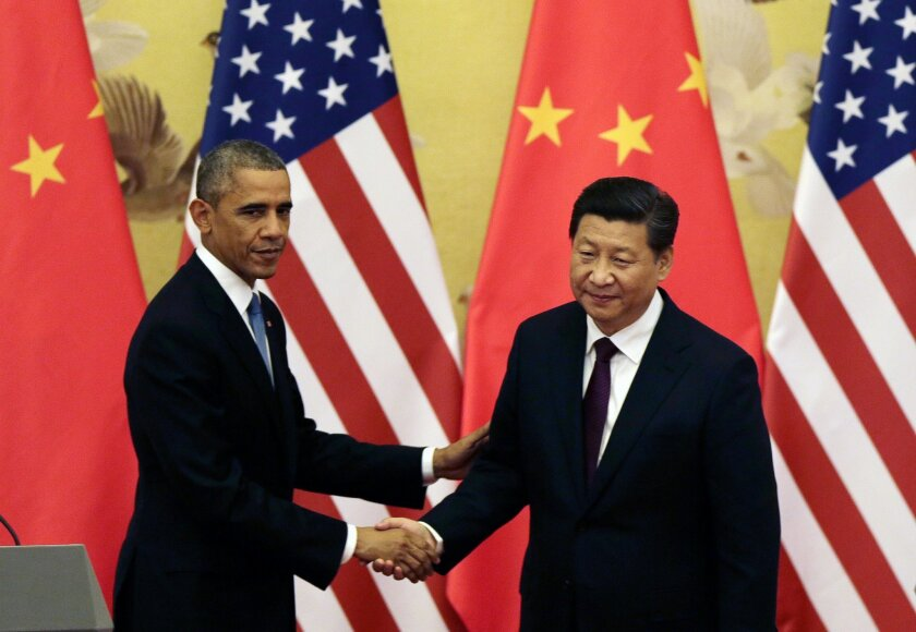 FILE - In this Nov. 12, 2014 file photo, U.S. President Barack Obama, left, shakes hands with his Chinese counterpart Xi Jinping after their press conference at the Great Hall of the People in Beijing, China. As Xi makes his first state visit to Washington this week, the outlook for relations is decidedly murkier than when he hosted Obama at their last summit less than a year ago. Tensions are rising over allegations of Beijing-directed cyberattacks on the U.S. and China's moves to assert its South China Sea territorial claims. (AP Photo/Andy Wong, File)