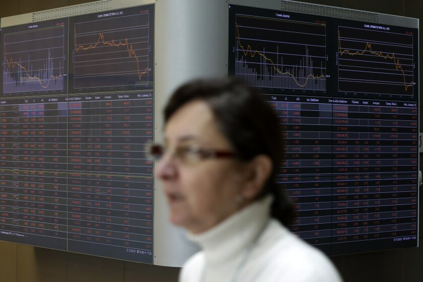 An employee passes next to an index board at the reception hall of the Stock Exchange in Athens, Thursday, Feb. 11, 2016. Banks, particularly in Europe, have come under pressure over recent days as investors fret about their ability to cope with a bigger than expected global slowdown at a time when