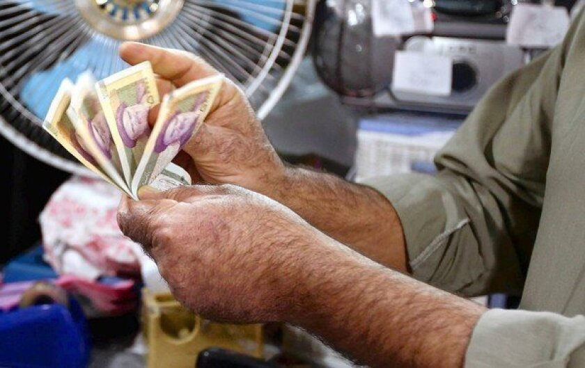 An Iranian counts his rial notes at a shop in Tehran. Hundreds of business owners marched in the capital in protests linked to rising prices and the currency's plunging value.