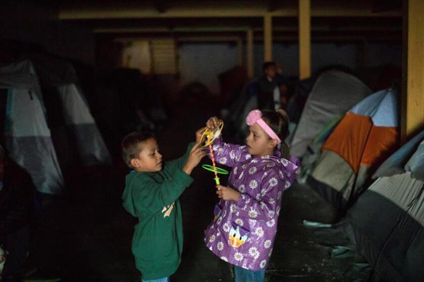 """Migrantes centroamericanos ubicados en el albergue """"Contra viento y marea"""" celebran Nochebuena tras una congregación religiosa- Activistas les obsequiaron regalos para hacer más llevadera la noche. EFE"""