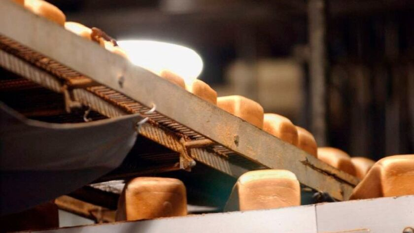 Loaves of white bread move on a conveyor belt at a food-production plant.