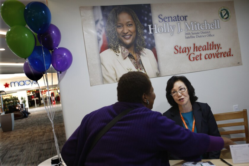 Helen Lee, right, an enrollment counselor, signs up a client for health coverage at a Covered California health insurance exchange office in Los Angeles.