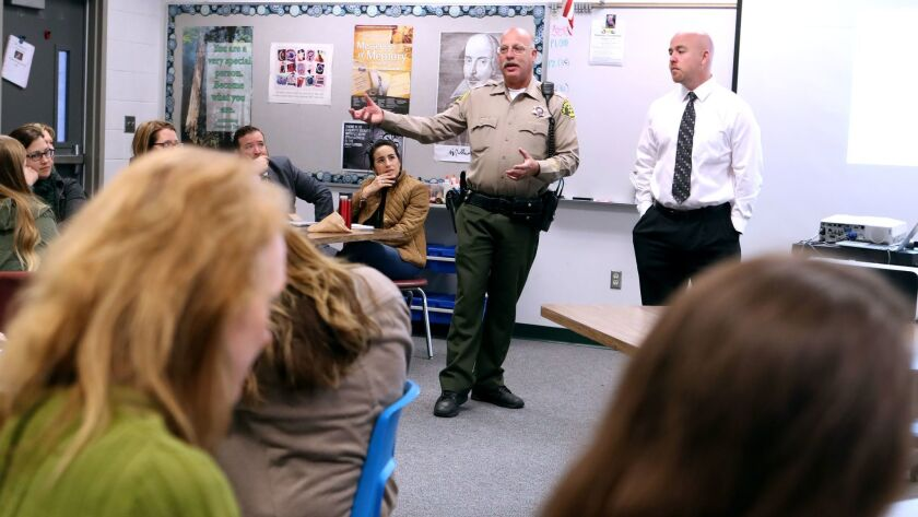 L.A. County Sheriff deputy Eric Matejka, left, speaks to La Canada High School 7/8 staff about activ