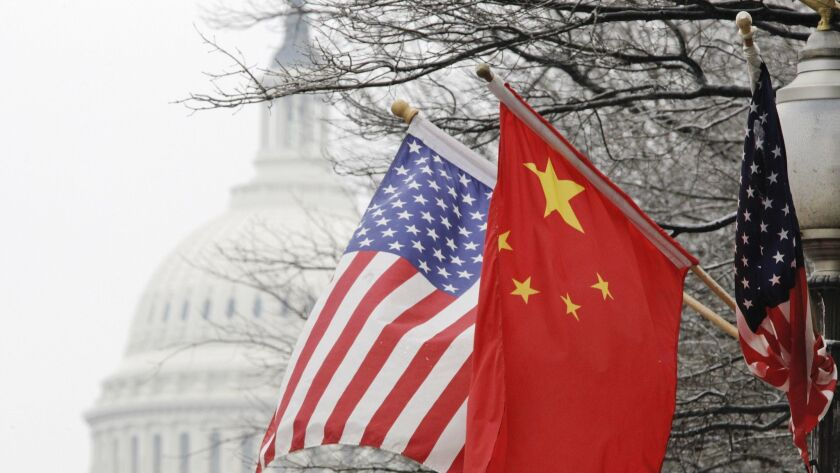 The Capitol dome is seen at rear as Chinese and U.S. flags are displayed in Washington, Tuesday, Jan