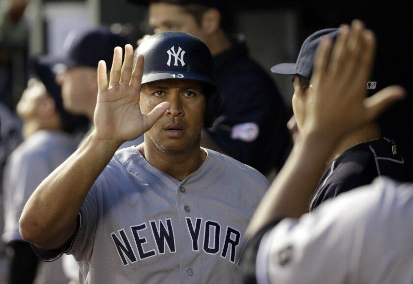 New York Yankees' Alex Rodriguez high-fives teammates in the dugout after scoring on a sacrifice groundout by Didi Gregorius in the fourth inning of a baseball game against the Baltimore Orioles in Baltimore, Saturday, June 4, 2016. (AP Photo/Patrick Semansky)