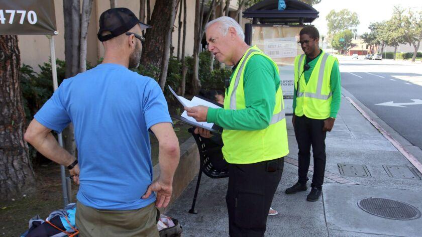 Bob Newman Ambassador Manager, center, and La Quentan McGuire, Ambassador Team Leader, assist people
