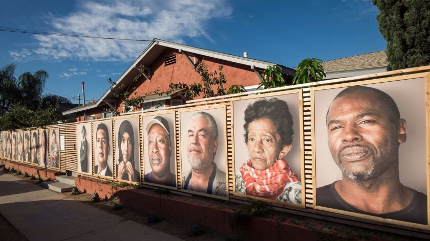 The fence of J. Raymond Mireles' Logan Heights house served as the outdoor canvas for photos he took of area residents. The photos are now at Bread & Salt.