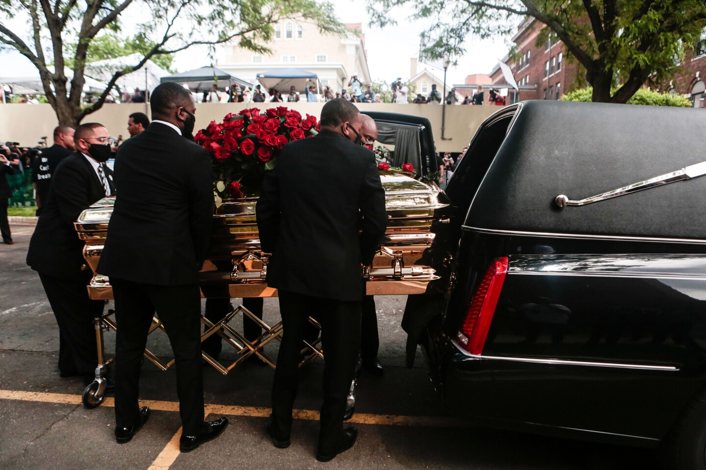 MINNEAPOLIS , MINNESOTA - JUNE 04: Hundreds of people cheer and chant as George Floyd's casket is placed into the hearse after his memorial service on Thursday, June 4, 2020 in Minneapolis , Minnesota. (Jason Armond / Los Angeles Times)