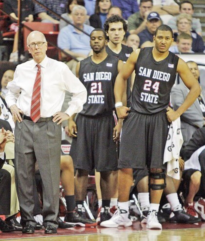 SDSU coach Steve Fisher (from left) and players Matt Thomas, Mehdi Cheriet and Tim Shelton watch from the bench as the Aztecs draw closer in the second half, only to fall just short. (Jae C. Hong / Associated Press)
