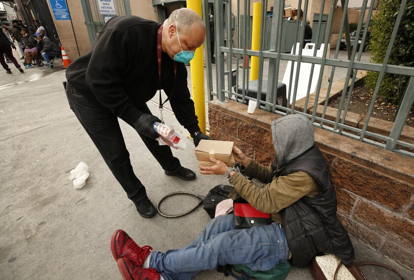 Ralph Sutton, an outreach coordinator at the Los Angeles Mission in skid row, hands Brent Kostanski a box of food.