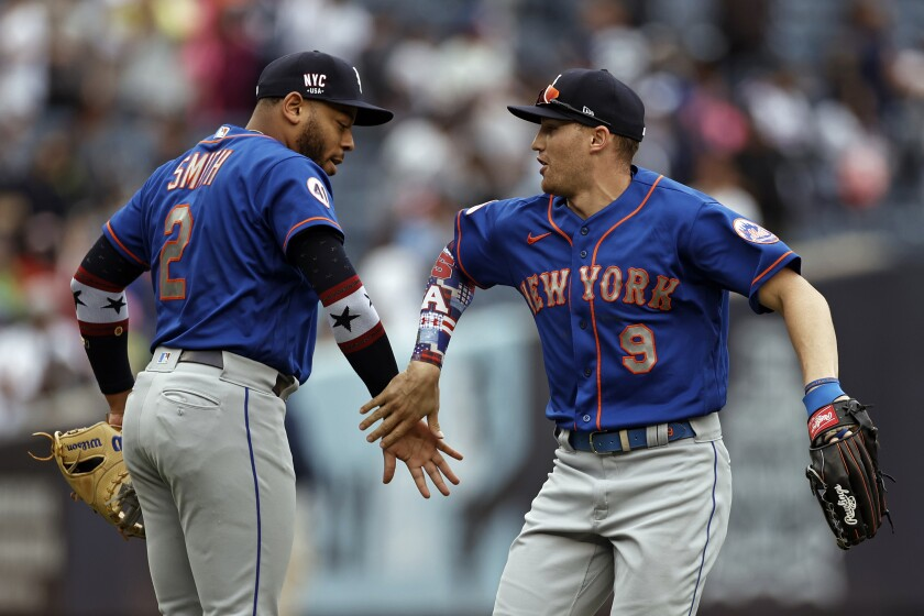 New York Mets center fielder Brandon Nimmo (9) and first baseman Dominic Smith (2) celebrate after defeating the New York Yankees in a baseball game Saturday, July 3, 2021, in New York. (AP Photo/Adam Hunger)