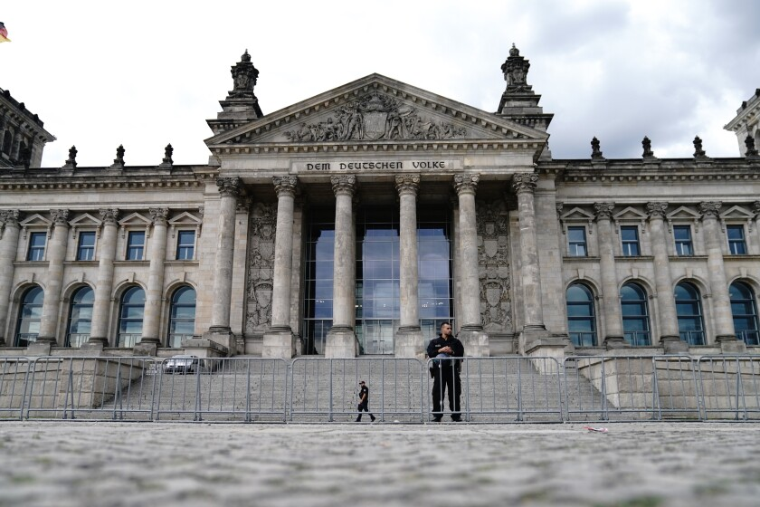 Police officers secure the Reichstag building behind cordon fences in Berlin, Germany, Aug. 30, 2020. Over the weekend, several tens of thousands of people demonstrated in the capital against the federal government's corona measures. This also led to clashes with the police. (Kay Nietfeld/dpa via AP)