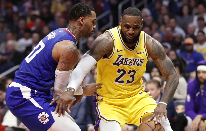 Lakers forward LeBron James spins to the basket against Clippers forward Mike Scott in the second quarter on Jan. 31 at Staples Center.