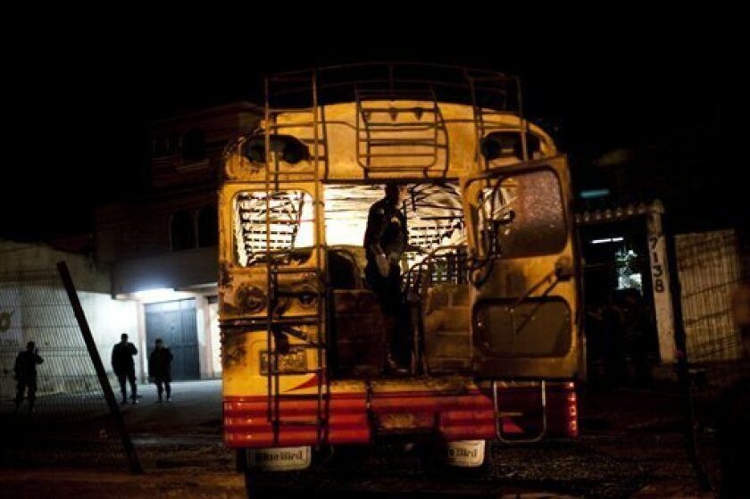 An investigator inspects a charred city bus where five people died and 16 were injured in Guatemala City, Monday Jan. 3, 2011. The cause of the explosion is unknown. (AP Photo/Rodrigo Abd)