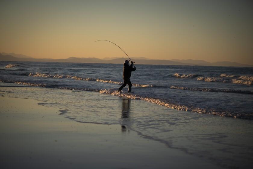 Una persona pesca en la playa en Cadiz, Andalucía, sur de España, el domingo 3 de enero de 2021