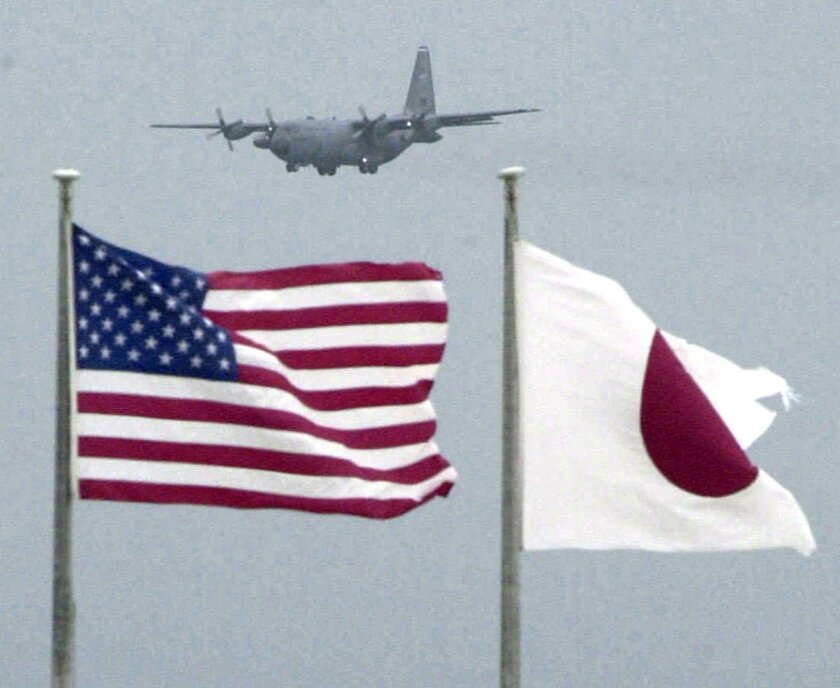 In this Sept. 23, 2001 photo,   flags of U.S. and Japan flutter in U.S. Kadena Air Base on the southern island of Okinawa in Japan.   An American sailor has tapped a cloud-based technology for mobile phones to make it easier to have volunteers take turns driving drunk friends home, an initiative th