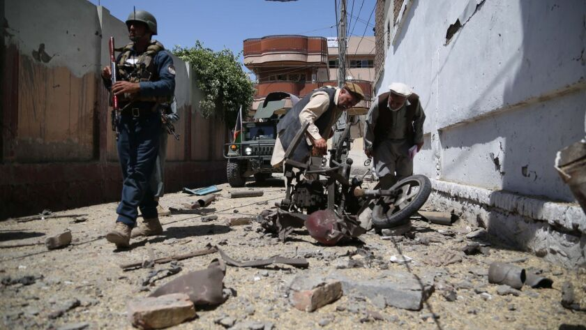 Afghan security officials inspect the scene of a bomb blast near a voter registration center in Jalalabad.