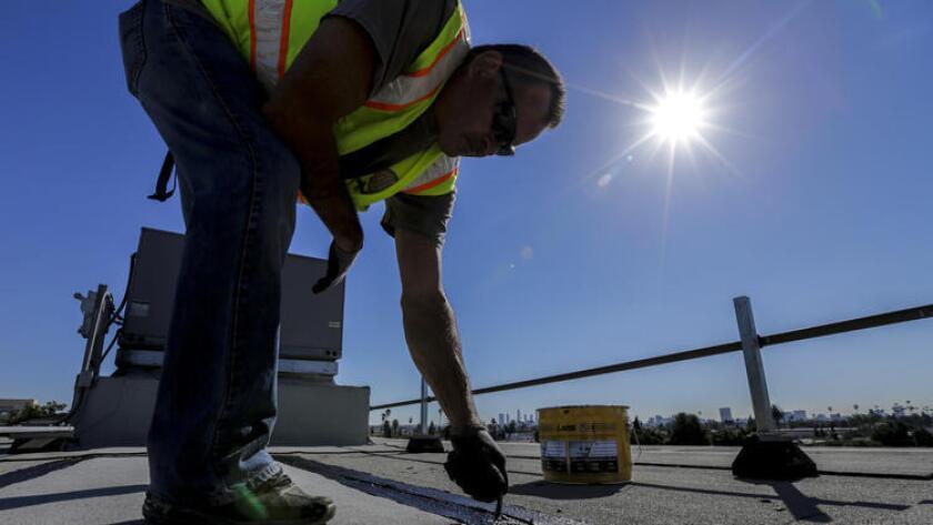 El pasado 3 de febrero, Rick Rodriguez, un trabajador del Distrito Escolar Unificado de Los Ángeles, sella una gotera sobre el techo del auditorio de Le Conte Middle School. (Irfan Khan / Los Angeles Times).