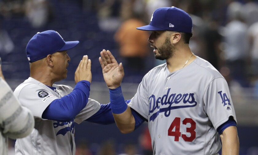 Dodgers manager Dave Roberts, left, high-fives Edwin Rios after defeating the Miami Marlins on Aug. 14 in Miami.