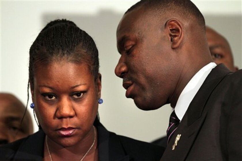 Trayvon Martin's mother Sybrina Fulton, left, listens to the family attorney Benjamin Crump, during a news conference at the Washington Convention Center in Washington, Wednesday, April 11, 2012. A law enforcement official says that charges are being filed in the shooting death of Trayvon Martin. The official with knowledge of the investigation says a prosecutor will announce charges against George Zimmerman on Wednesday at 6 p.m. Zimmerman's arrest is also expected soon. (AP Photo/Jacquelyn Martin)