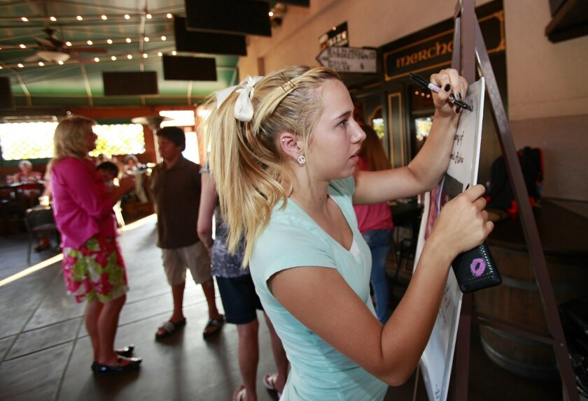 Brianna Wray, 16, signs a poster for Alyssa Collier during a fundraiser for Collier at Hooley's Irish Pub & Grill in Rancho San Diego.