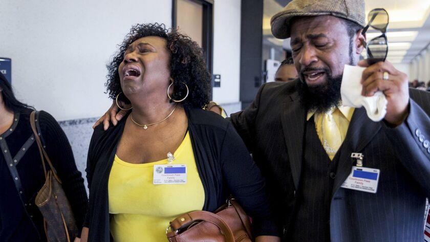 Kattie Jones and her husband, Clinton Jones, Sr., father of Corey Jones, walk down the hall from the