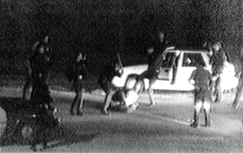 Shortly after midnight on March 3, 1991, LAPD officers converge on a Hyundai in Lake View Terrace. Their beating of its driver, Rodney King, was captured on videotape by George Holliday.