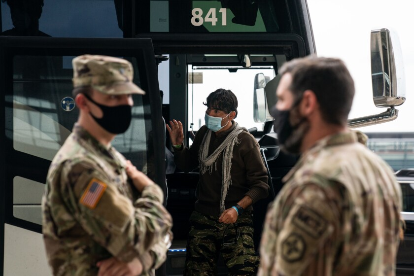 Evacuees who fled Afghanistan board buses on Tuesday, Aug. 31, 2021.