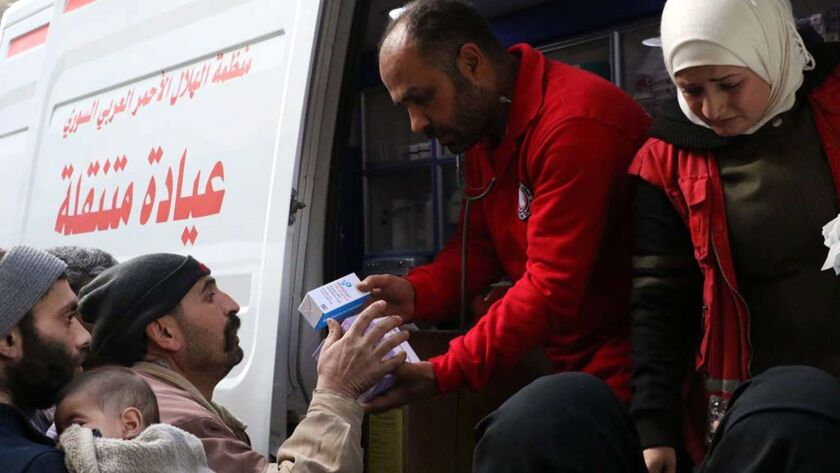 Volunteers distribute medical supplies to Syrians in Duma, in the east Ghouta region, on March 5, 2018.