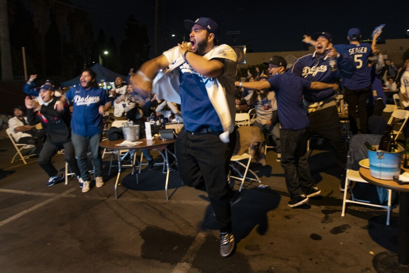 Dodgers fans jump and pump their fists at tables set up in an outdoor parking lot