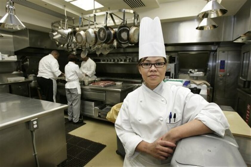 """This Dec. 12, 2006 file photo shows White House Chef Cristeta Comerford as she pauses during preparation for a meal in the White House kitchen in Washington. As tempting as it may be to see the Obama family's choice as the ultimate """"Top Chef"""" reality show, former White House executive chef Walter Scheib believes there's a 90 percent chance the new administration will stick with his successor, Cristeta Comerford. (AP Photo/Ron Edmonds, FILE)"""
