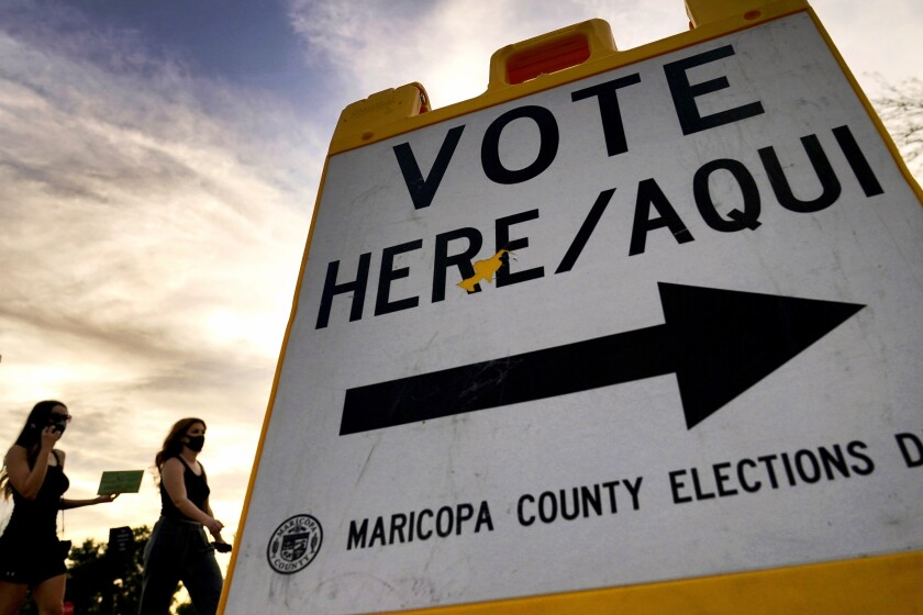 Voters deliver their ballot to a polling station in Tempe, Ariz.