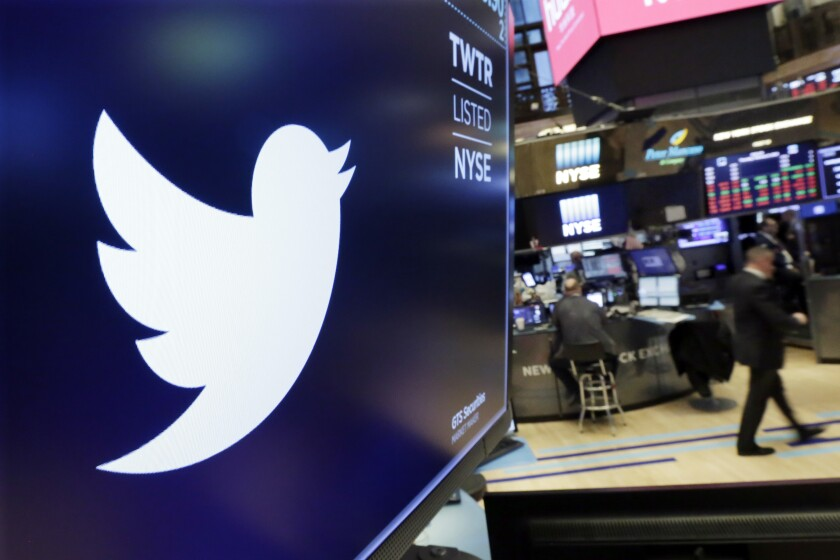 The logo for Twitter is displayed above a trading post on the floor of the New York Stock Exchange.
