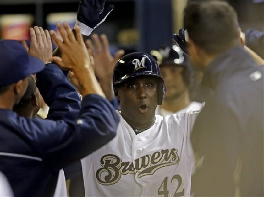 Milwaukee Brewers' Yuniesky Betancourt celebrates in the dugout after hitting a grand slam during the third inning of a baseball game against the San Francisco Giants on Tuesday, April 16, 2013, in Milwaukee. (AP Photo/Morry Gash)